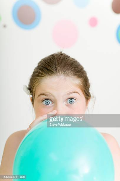 Girl (9-11) blowing up balloon