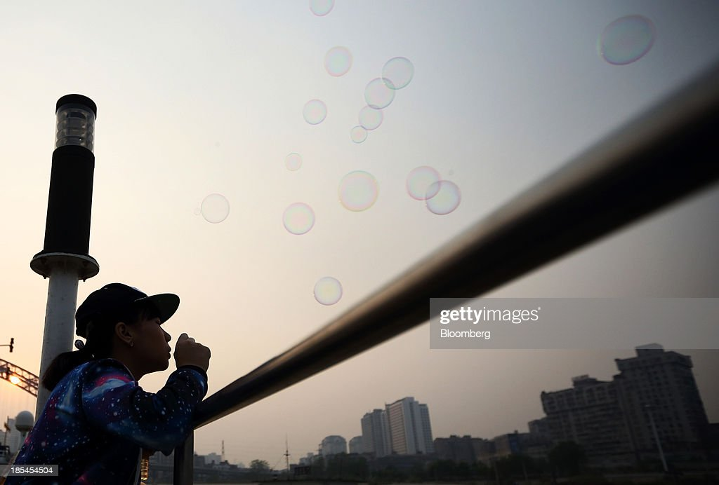 A girl blows soap bubbles on a ferry crossing the Chang Jiang river in Wuhan, China, on Sunday, Oct. 20, 2013. China's economic expansion accelerated to 7.8 percent in the third quarter from a year earlier, the statistics bureau said Oct. 18, reversing a slowdown that put the government at risk of missing its 7.5 percent growth target for 2013. Photographer: Tomohiro Ohsumi/Bloomberg via Getty Images