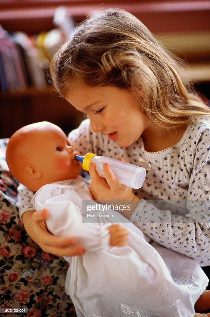 Girl (4-6) bottle feeding doll, indoors : Stock Photo