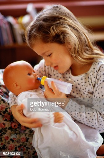 Girl (4-6) bottle feeding doll, indoors