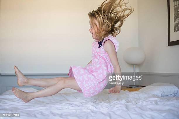 Girl bouncing on her bed