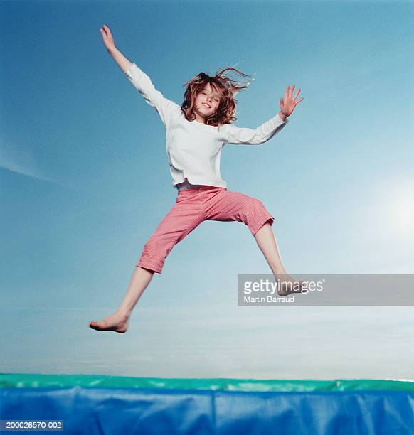 Girl (8-10) bouncing on trampoline
