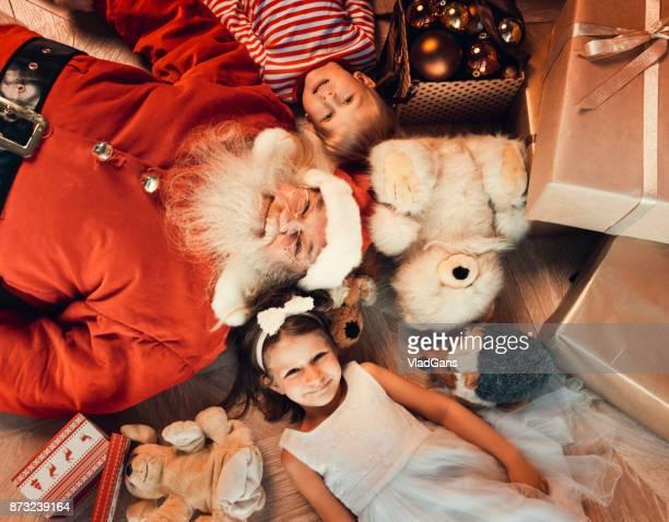 Girl, boy and santa lie on the floor