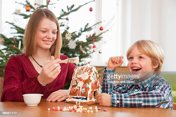 girl, boy decorating gingerbread house