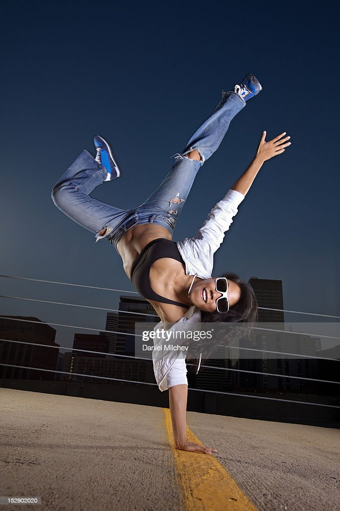 Girl breakdancing on a rooftop. : Stock Photo