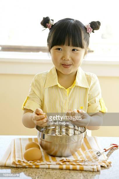 Girl breaking egg into bowl