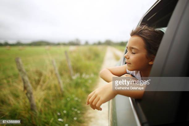 A girl breathing air through the window of a car