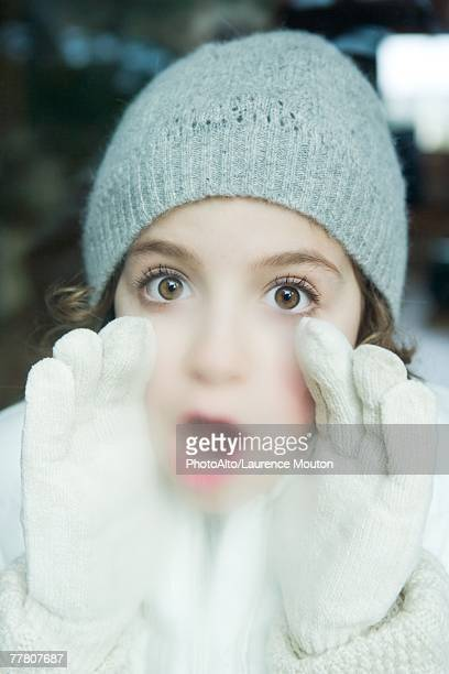 Girl breathing on window, dressed in winter clothing, looking at camera, portrait
