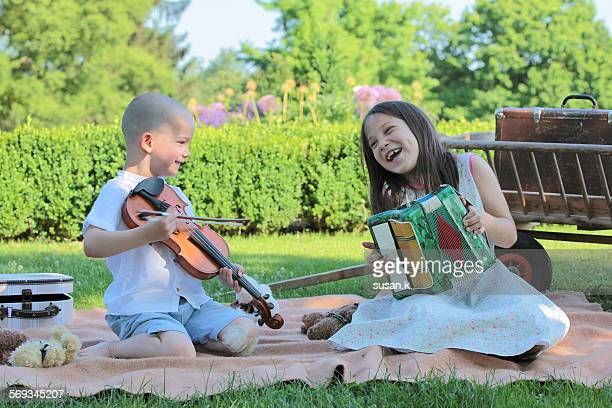 Girl & brother playing musical instruments outdoor