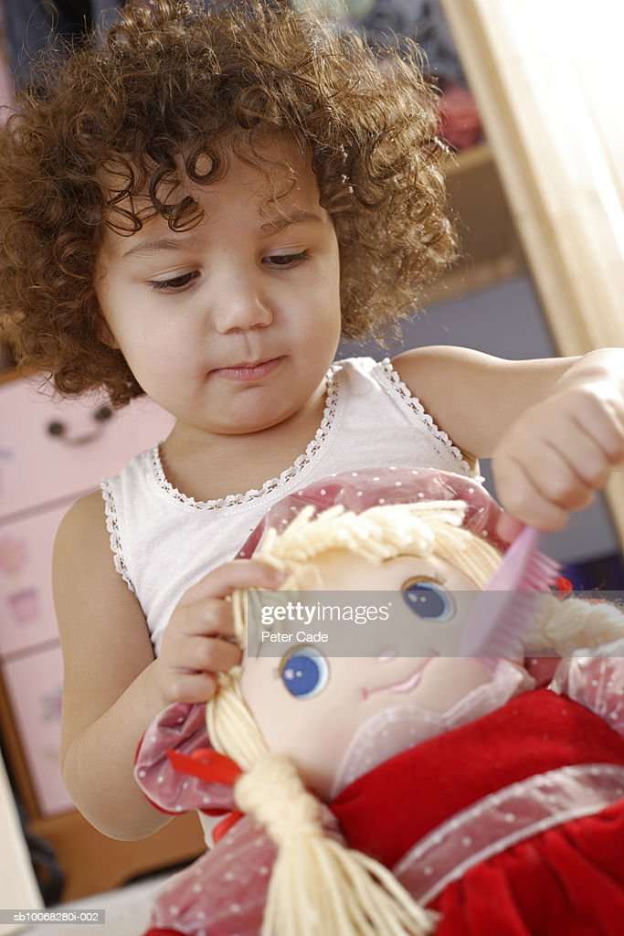 Girl (2-3) brushing doll's hair, close-up : Stock Photo