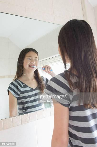Girl brushing her teeth in bathroom mirror