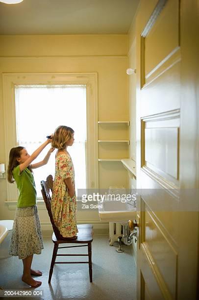 Girl (7-9) brushing sister's (4-6) hair, side view
