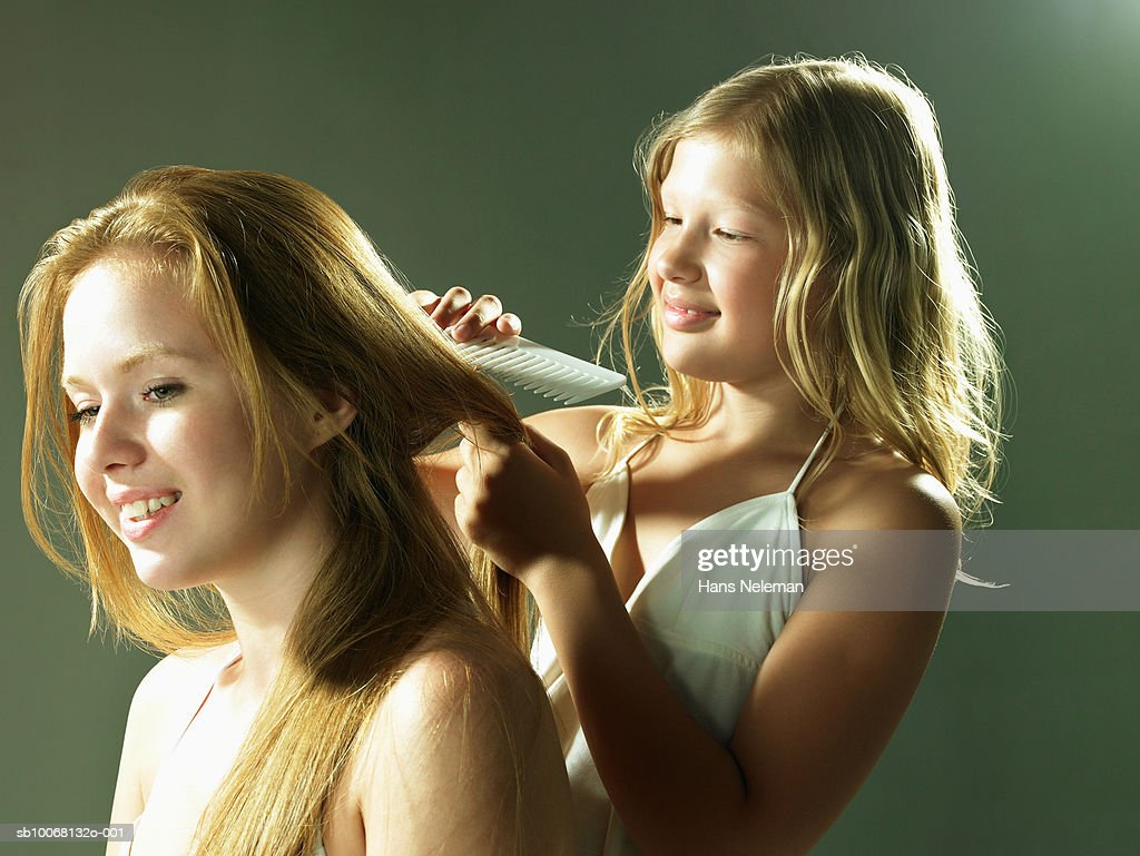 Girl (8-9) brushing sister's (12-13) hair, studio shot : Foto de stock