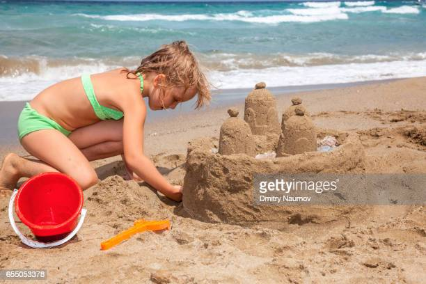 Girl building a sandcastle on a beach