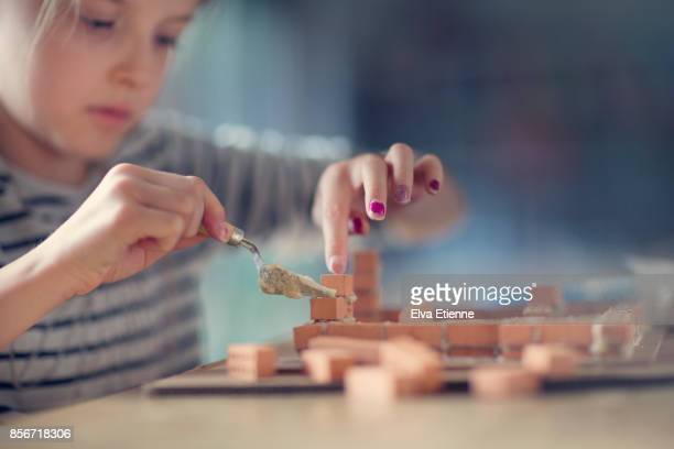 Girl (10-11) building miniature house from bricks