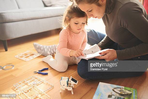Girl building solar robot with mom