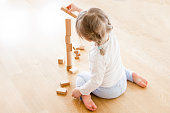 Little girl (two years old) is sitting on the floor and playing with her building blocks. She is building a high tower and are just about to put another block to it. She is sitting with her back again