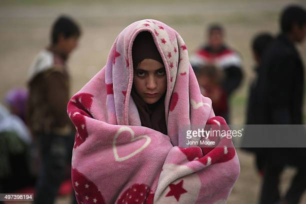 A girl bundles against the cold while fleeing an ISIL or Daeshheld frontline village on November 16 2015 to Sinjar Iraq Peshmerga forces carefully...