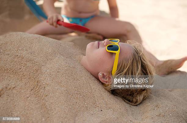 Girl buried in sand by her sister