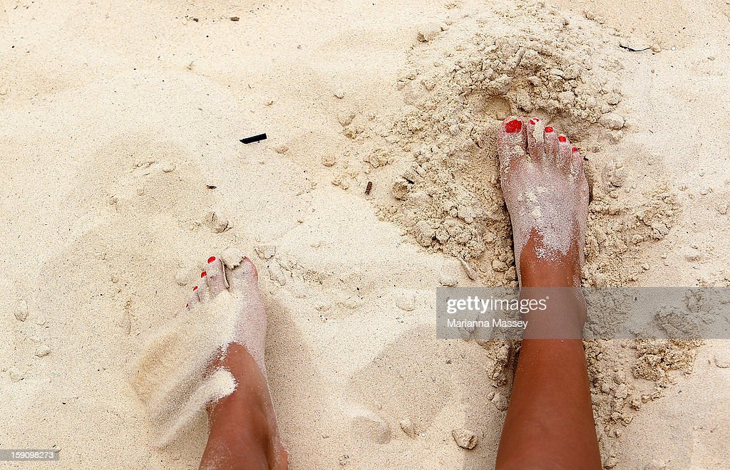 A girl buries her feet in the sand to keep them cool at Bondi Beach on January 8, 2013 in Sydney, Australia. Temperatures are expected to reach as high as 43 degrees around Sydney today.