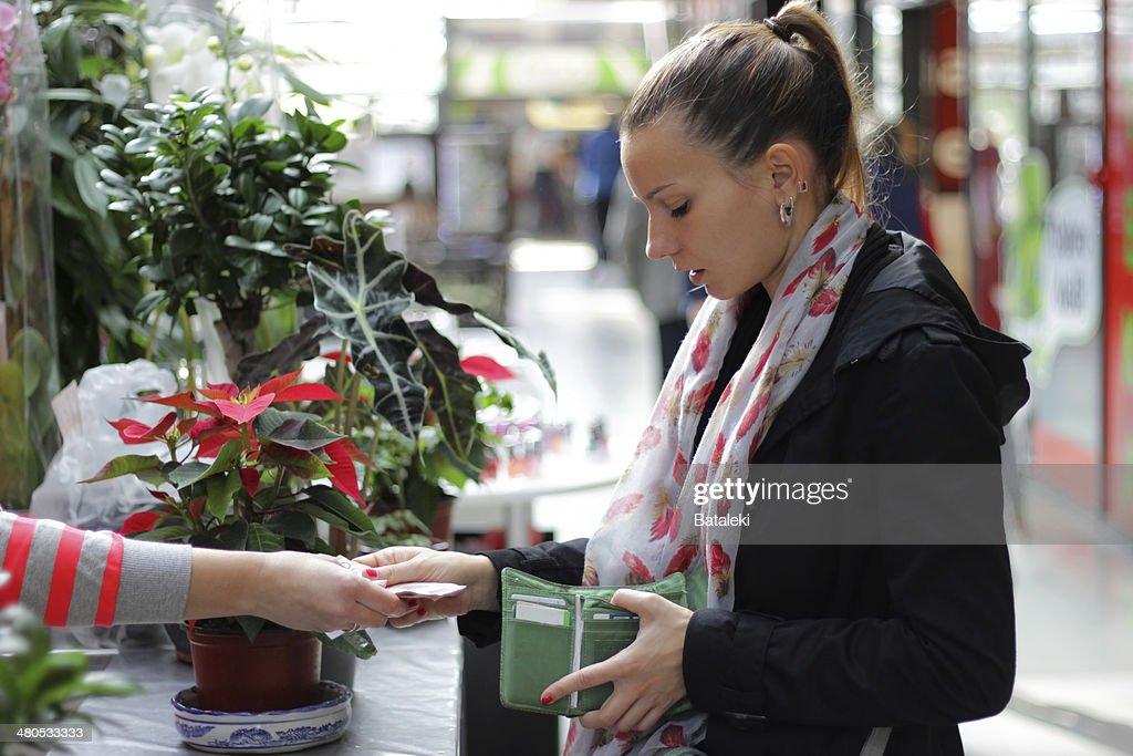 Girl buying flowers : Stock Photo