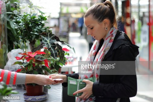 Girl buying flowers : Stock Photo