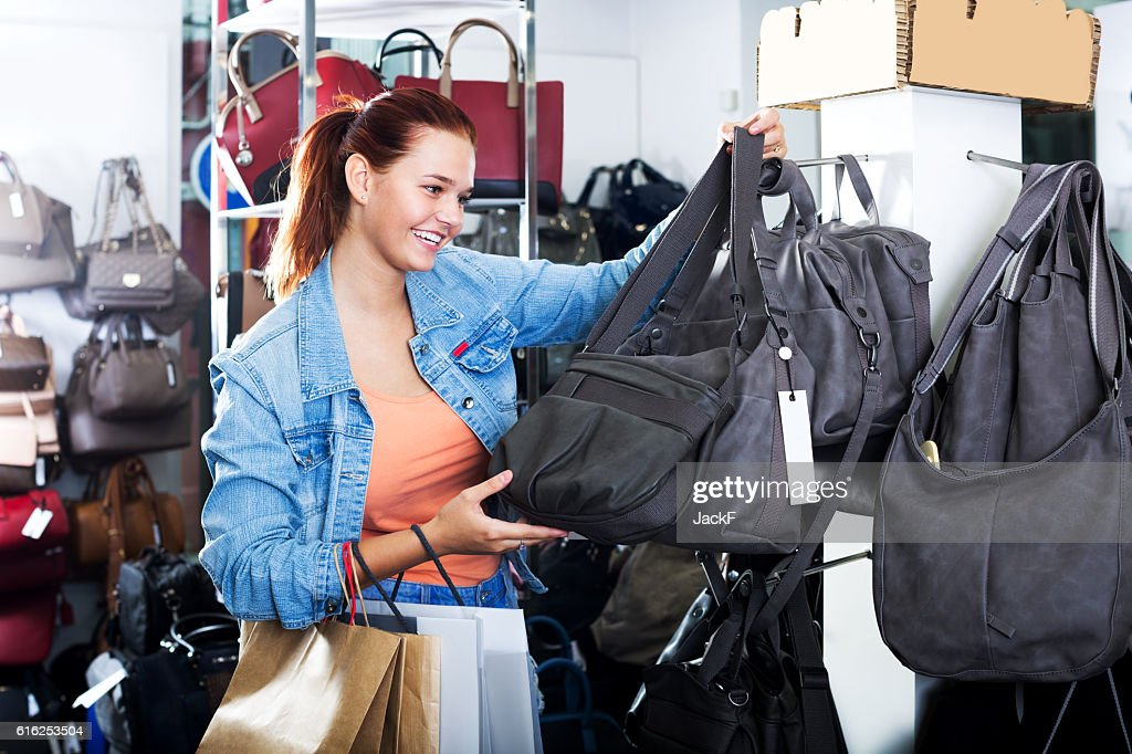Girl buying handbag in fashion shop : Foto de stock