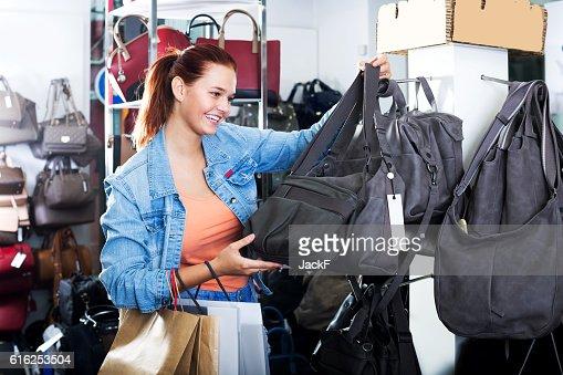 Girl buying handbag in fashion shop : Foto de stock