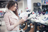 Girl buying sneakers at shopping mall