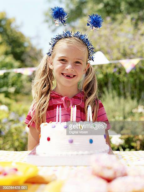 Girl (3-5) by birthday cake outdoors, smiling, portrait