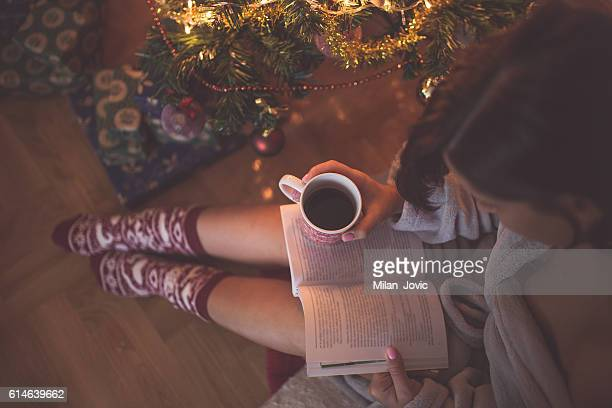 Girl by christmas tree with coffee cup reading a book