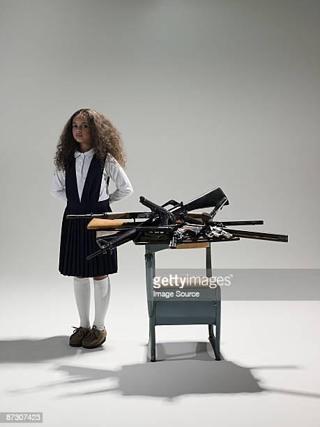 Girl by guns on desk