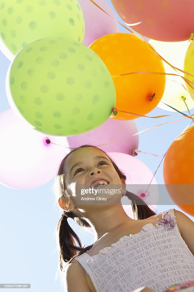 Girl (5-7) by helium balloons, smiling, low angle view : Stock Photo