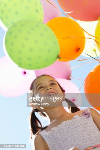 Girl (5-7) by helium balloons, smiling, low angle view : Photo