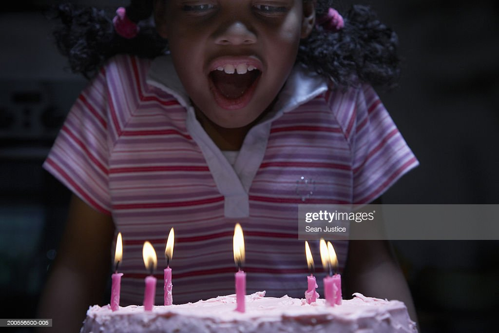 Girl (8-10) by pink birthday cake : Stock Photo
