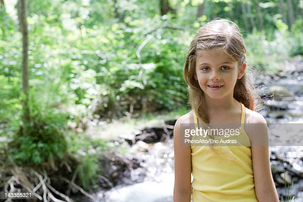 Girl by stream in woods, portrait