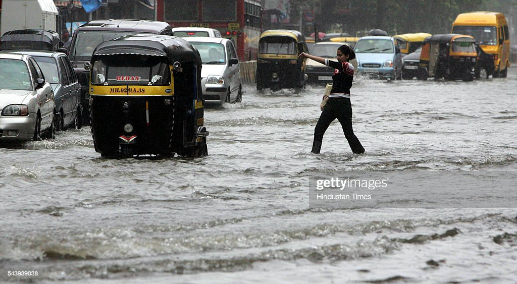 A girl calling for an auto to take her out of the logged water on Linking Road, Bandra on July 31, 2005 in Mumbai, India.