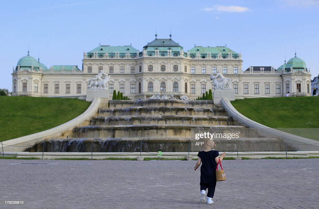 A girl carries a bag as she walks on sunny day in the gardens of the Belvedere Palace in Vienna on June 9, 2013. Meteorologists forecast temperatures around 25 degrees for central Austria.