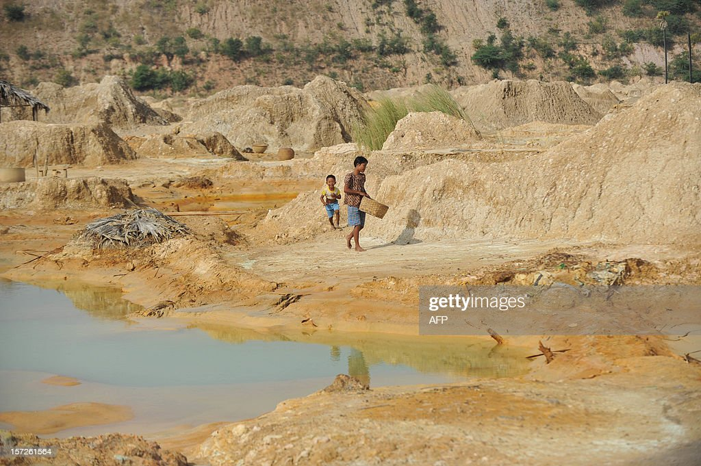A girl carries a bag of sulphur sand to make copper with at a copper mine waste dump in Sarlingyi township December 1, 2012. Myanmar is one of the poorest countries in Asia after decades of economic mismanagement and isolation under army rule.