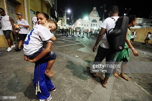 A girl carries a boy on the first day of Carnival celebrations on February 16 2012 in Salvador Brazil Carnival is the grandest holiday in Brazil...
