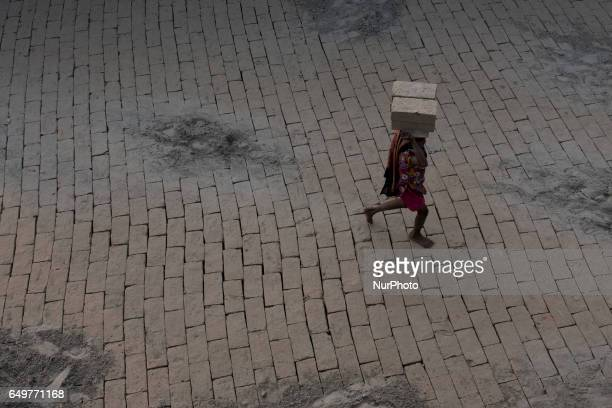 Girl carries a heavy pile across the kiln Kamduni West Bengal India 080317 The brick kilns of Bengal employ a large number of laborers from distant...