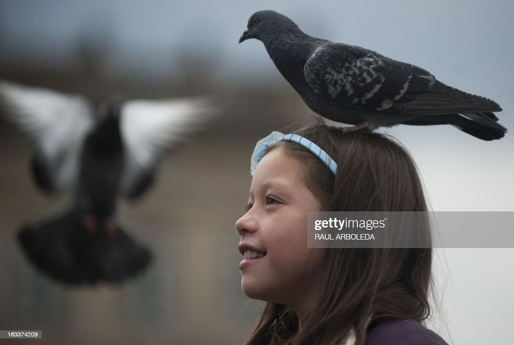 A girl carries a pigeon on her head in Bogota, Colombia, during the commemoration of the International Women's Day on March 8, 2013. AFP PHOTO/Raul ARBOLEDA /
