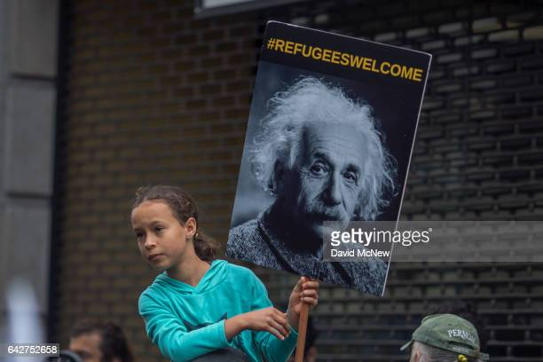 A girl carries a sign in the Immigrants Make America Great March to protest actions being taken by the Trump administration on February 18 2017 in...