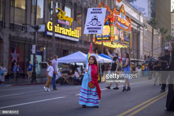 A girl carries a sign on Hollywood Boulevard near the El Capitan Theatre and the Jimmy Kimmel Live Studio during an event celebrating Indigenous...