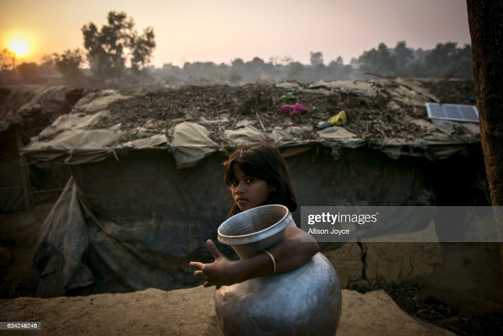 COX'S BAZAR, BANGLADESH - FEBRUARY 8: A girl carries a water jug in Kutapalong Rohingya refugee camp on February 8, 2017 in Cox's Bazar, Bangladesh. The United Nations estimates about 69,000 Rohingya Muslims have fled to Bangladesh from Myanmar since October last year after the Burmese army launched a campaign it calls 'clearance operations' in response to an attack on border police. Based on reports, Bangladesh plans to proceed with a controversial plan to relocate tens of thousands of Rohingya refugees from Myanmar to a remote island in Bay of Bengal, despite warnings it is uninhabitable and prone to flooding. Waves of Rohingya civilians have fled across the border since last year, most living in makeshift camps and refugee centers with harrowing stories on the Burmese army committing human-rights abuses, such as gang rape, arson and extrajudicial killing. The Rohingya, a mostly stateless Muslim group numbering about 1.1 million, are the majority in Rakhine state and smaller communities in Bangladesh, Thailand and Malaysia.