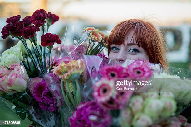A girl carries flowers to make a flower wall as part of an Amnesty international vigil in front of a flower wall that reads '#keephopealive' for the...