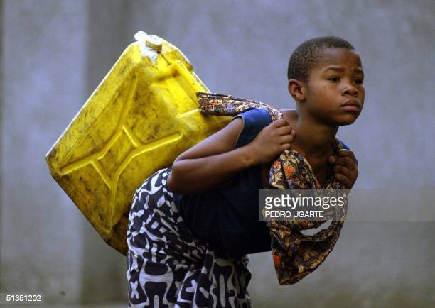 A girl carries potable water to her home 25 January 2002 in Goma a week after a volcanic eruption devastated the town Lava gushing from Mount...