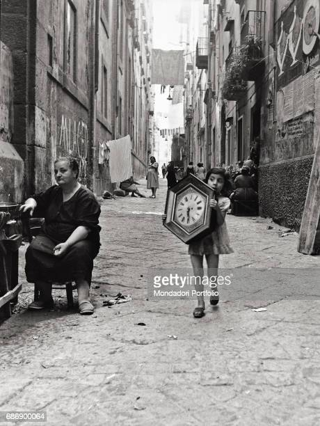 A girl carrying a clock in a Neapolitan alley This picture is taken from the monography 'Mario De Biasi Il mio sogno Š qui' curated by Enrica Vigan•...