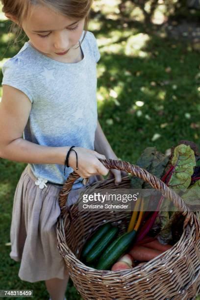 Girl carrying basket of vegetables