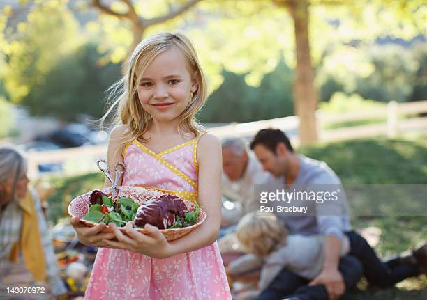 Girl carrying bowl of salad outdoors